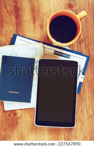 top view of tablet with empty screen, passport and boarding pass over wooden table. travel concept - stock photo