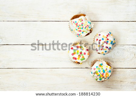 Top view of tasty cupcakes on a white wooden background  - stock photo