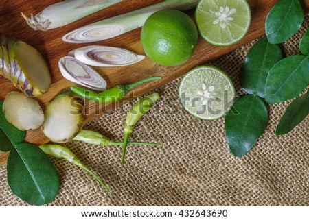 Top view of Thai food ingredients, herbs on wood and burlap background. Green chili, galanga, lime, kaffir lime leaves, lemongrass. Spicy soup ingredients. - stock photo