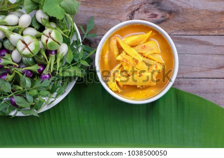 Top view of Thai hot and sour spicy yellow soup and fresh sea fish in the white bowl with vegetable ,on banana leaf and wooden table , With copy space.