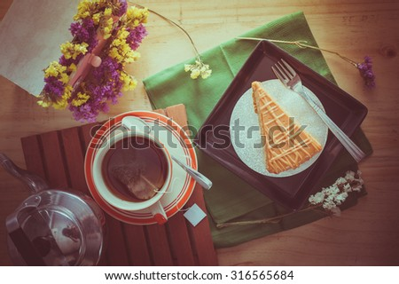 Top view of Thai tea cake on black ceramic dish with a cup of hot tea in morning time with film filter effect - stock photo