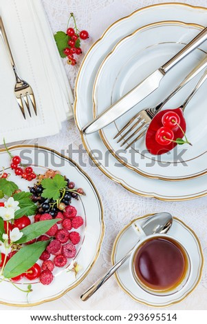 Top view of the beautifully decorated table with cup of tea, white plates with different berries, linen napkin, cutlery and flowers on luxurious tablecloths - stock photo