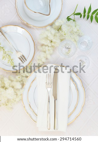 Top view of the beautifully decorated table with white plates, crystal glasses, linen napkin, cutlery and flowers on luxurious tablecloths - stock photo