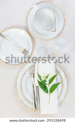 Top view of the beautifully decorated table with white plates, crystal glasses, linen napkin, cutlery and jasmine flower on luxurious tablecloths - stock photo