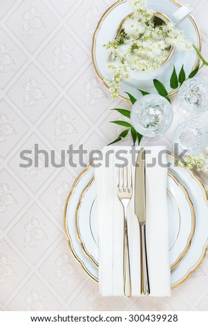 Top view of the beautifully decorated table with white plates, crystal glasses, linen napkin, cutlery and white flower on luxurious tablecloths, top view, with space for text - stock photo