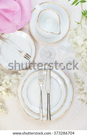 Top view of the beautifully decorated table with white plates, crystal glasses, pink linen napkin, cutlery and flowers on luxurious tablecloths - stock photo