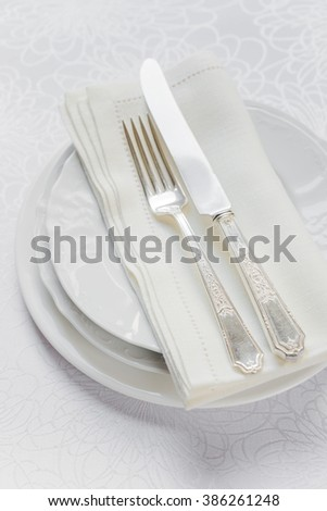 Top view of the beautifully decorated table with white plates, linen napkin  and cutlery on luxurious tablecloths - stock photo