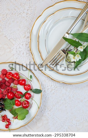 Top view of the beautifully decorated table with white porcelain plates with different berries, cutlery and flowers on luxurious tablecloths, with space for text - stock photo