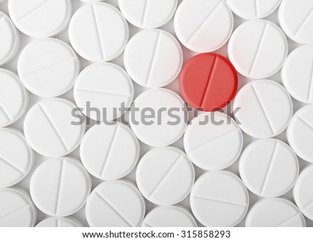 Top view of the heap of white medicine pills on white surface. One red medicine tablet is as a concept of a vaccine.