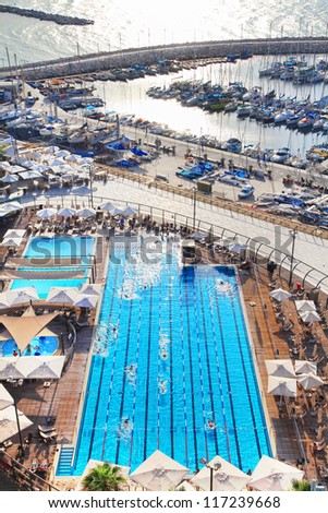 Top view of the out-door pool with swimming people in the blue water in autumn evening on the Mediterranean coast and marine background. Tel Aviv, Israel - stock photo