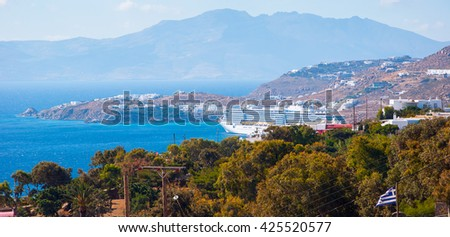 Top view of the sea, green trees and Mykonos port with cruise ship.