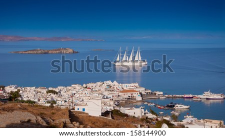 Top view of the town and port of Mykonos Island and a sailing ship in the blue sea ...
