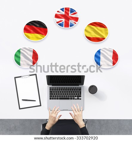 Top view of the working place with woman's hands. A laptop, notepad and a cup of coffee are on the table. Italian, German, United Kingdom, Spanish and French flags in the bubbles. - stock photo