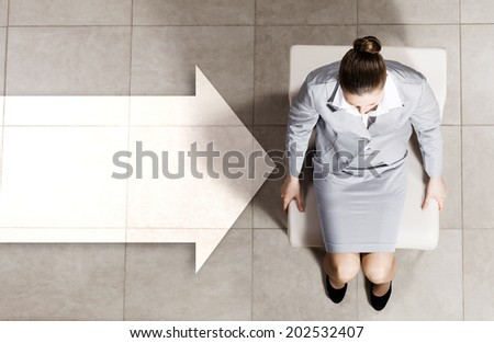 Top view of thoughtful businesswoman sitting on chair