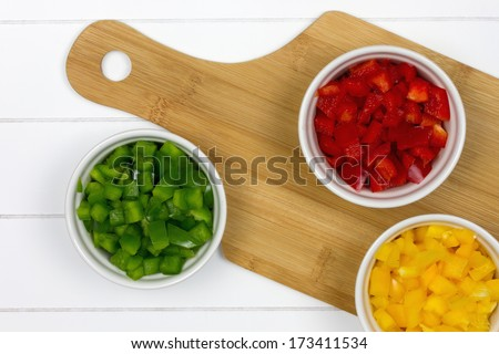 top-view of three bowls filled with sliced bell peppers on a cutting board - stock photo