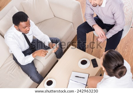 Top view of three business people are sitting at the table and discussing something with coffee. - stock photo