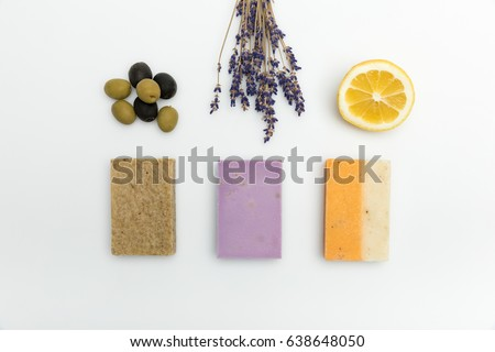 Top view of three types on homemade soap with dried lavender, olives and lemon isolated on white