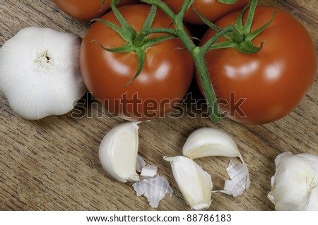 Top view of tomatoes and garlic on a wooden table top. - stock photo