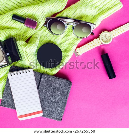 Top view of  trendy   spring  accessories  of modern woman on pink floor. Neon sweater , yellow wrist watch,glasses, lipstick, nail polish, perfume, electronic book and notepad.  - stock photo