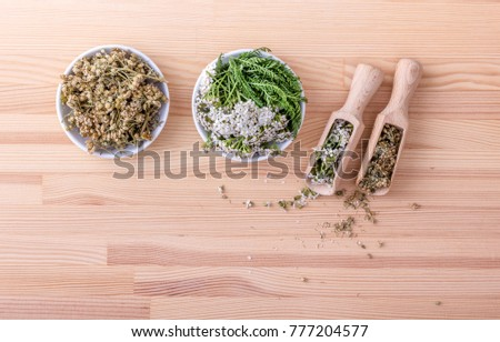 Top view of two bowls and spoons of fresh and dried flowers and leaves of yarrow with a wooden background