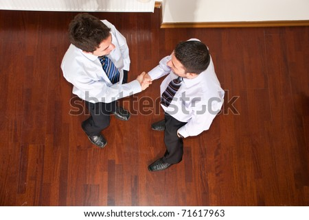 Top view of two business men giving hand shake and congratulate each other - stock photo