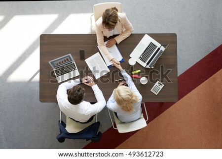 Top view of two businesswomen shaking hands after successful business deal while sitting at desk in the office.