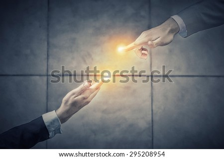 Top view of two businesswpeople reaching fingers to touch each other - stock photo