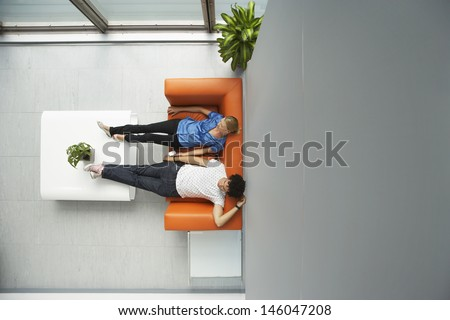 Top view of two casual people reclining on couch in reception room at office - stock photo