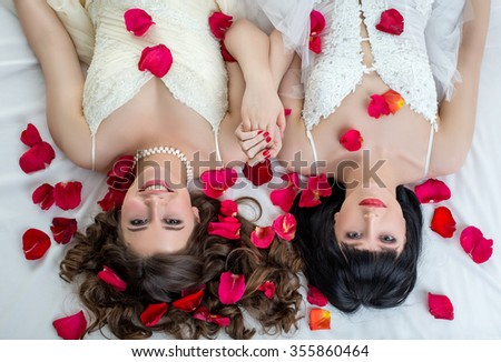 Top view of two charming brides looking at camera - stock photo