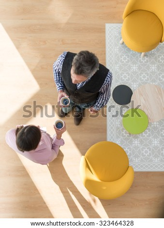 Top view of two co-workers having a break in a stylish vintage living room with wooden floor. The grey hair man and the woman are standing next to two orange seats, holding their coffee and talking - stock photo