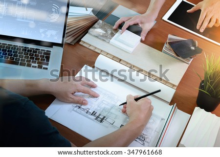 top view of two colleagues interior designers discussing data with blank screen new modern computer laptop and pro digital tablet with sample material on wooden desk as concept - stock photo