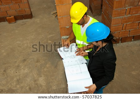 Top view of two construction workers people looking on projects in a house under construct - stock photo