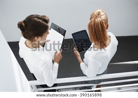 Top view of two female are holding touch pad and paper documents with copy space for your advertising text message. Woman manager is using tablet, while is standing with business partner in hallway - stock photo