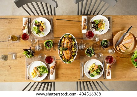 Top view of two roasted chicken in a bowl on lunch table. High angle view of dining table with salad and red wine. - stock photo
