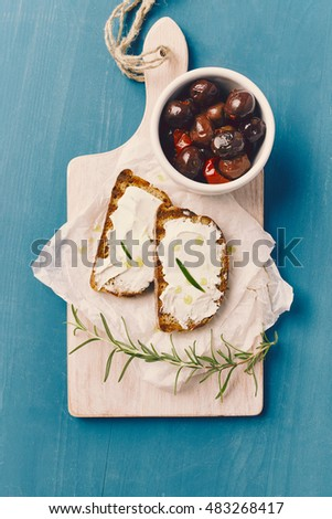 top view of two slice of grilled bread with spreadable cheese and oil on a white chopping board, on a blue wooden table, with olives in a white bowl an rosemary