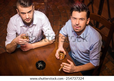Top view of two young men are drinking whisky and smoking cuban cigar.