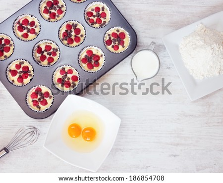 Top view of unripe muffins with ingredients. Two yolks, flour and milk placed on wooden white table. Space for text in the lower right corner. - stock photo