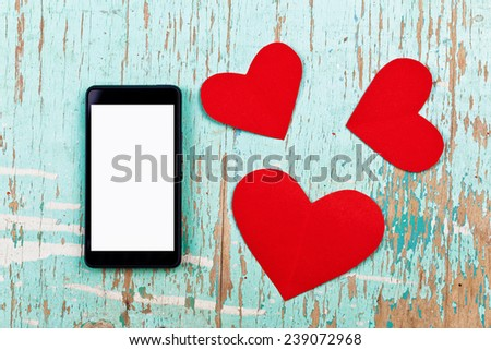 Top View of Valentine's Day copy space on smart phone with blank screen and red paper hearts on old grunge wood texture. - stock photo