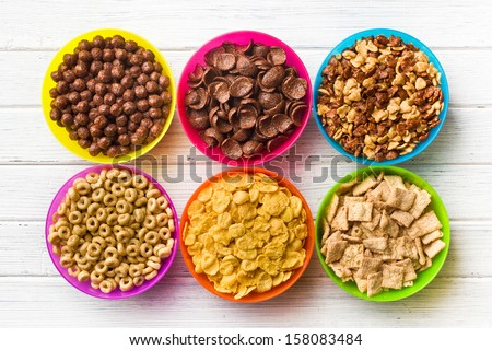 top view of various kids cereals in colorful bowls on wooden table - stock photo