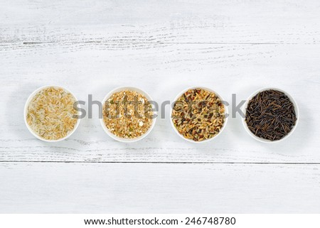 Top view of various rice types each within a small bowl on white wood - stock photo