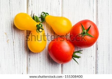 top view of various tomatoes on wooden table - stock photo