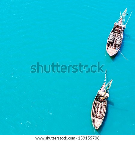 Top view of vintage boats in cyan blue transparent sea water  - stock photo