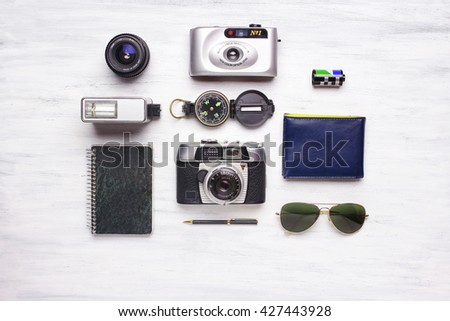 Top view of vintage camera and travel items, on a white wooden background. Travel and adventure concept. - stock photo