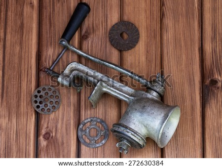 Top view of vintage old mincer with different metal nozzle on wooden background - stock photo