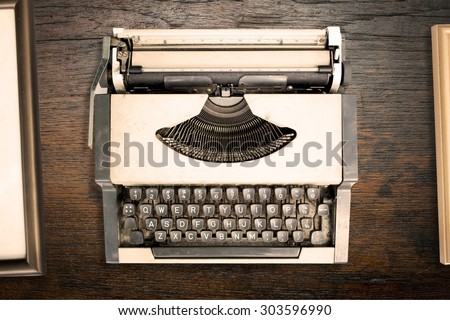 Top view of vintage typewriter with old frame on wooden texture background. retro style - stock photo