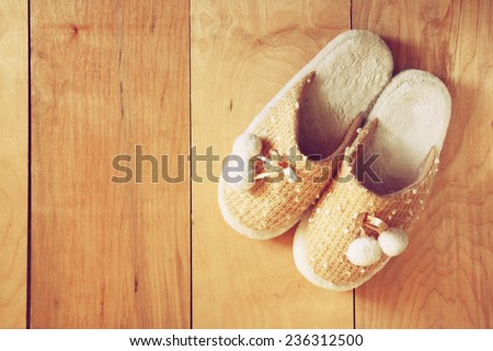 top view of warm woman slippers over wooden floor - stock photo
