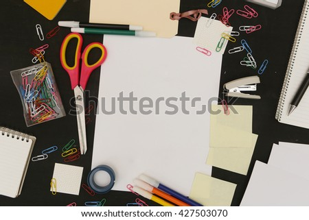 Top view of white blank paper surrounded with school or office equipment