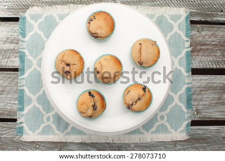 top view of white cake stand with fresh homemade blueberry whole wheat muffins on a blue and white place mat - stock photo