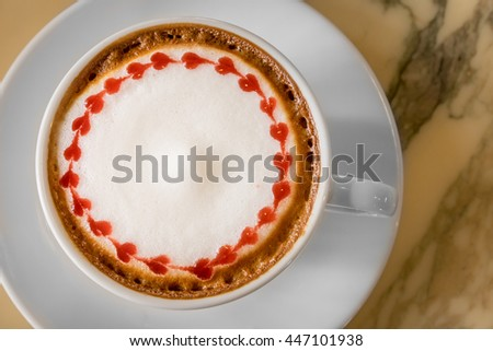 Top view of white ceramic cup of hot cappuccino coffee with holder on the right side. The item is on light yellow marble table top with plate coaster - stock photo