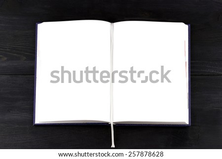 Top view of white notebook on dark wooden background